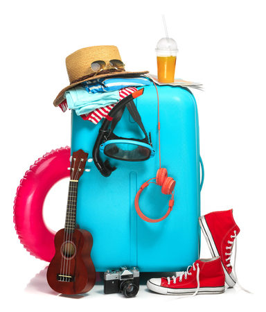 rubber ring: The blue suitcase, sneakers, hat and rubber ring on white background. The travel, tourism and holidays concept