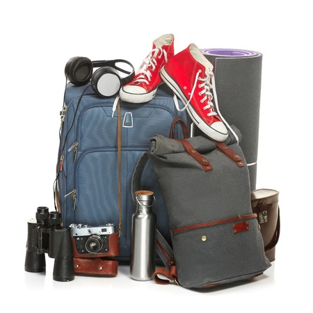 karemat: The suitcases, sneakers, retro camera, karrimat and binoculars on white background. The travel, tourism and holidays concept Stock Photo