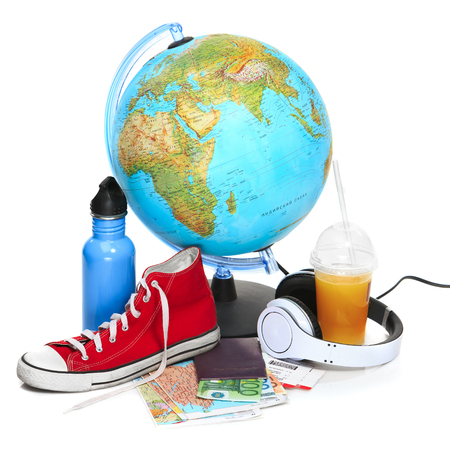 The blue globe, sneakers and headphones on white background. The travel, tourism and holidays concept