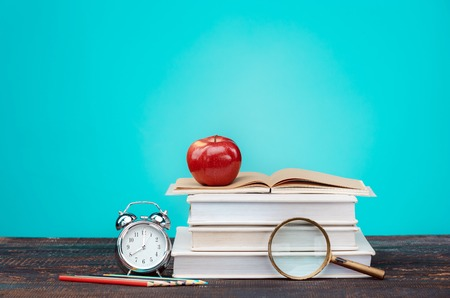učebnice: Back to School concept.School Books, colored pencils and clock on blue background