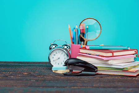 engrapadora: Back to School concept. Books, colored pencils and clock on blue background
