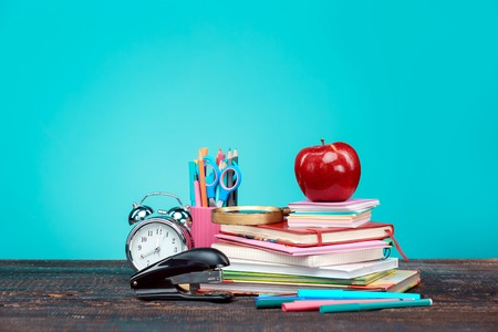 Back to School concept. Books, colored pencils and clock on blue background