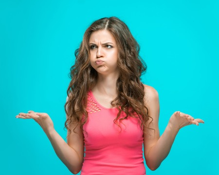 is disgusted: The portrait of disgusted woman on blue background. the concept of heavy choice