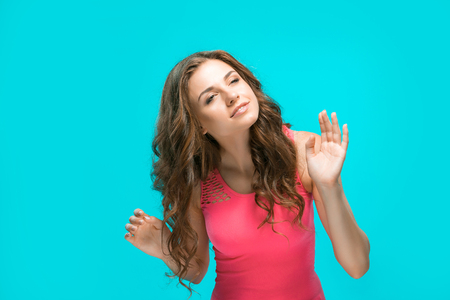 The young womans portrait with happy emotions on blue background
