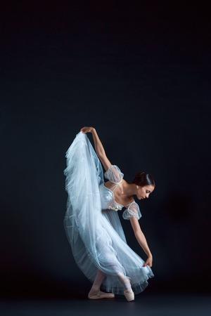 Portrait de la ballerine classique en robe blanche sur fond noir