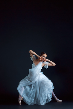 Portrait of the classical ballerina in white dress on the black background Stock Photo