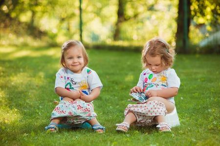 Les deux petites filles de bébé de deux ans assis sur des pots contre l'herbe verte