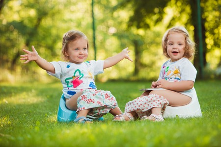 concentrates: The two little baby girls two-year old sitting on pots against green grass