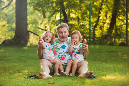 3 year old: Portrait Of Grandfather With Granddaughters against green grass