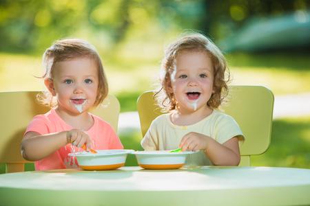 Twee kleine 2 jaar oude meisjes zitten aan een tafel en samen eten tegen een groen gazon