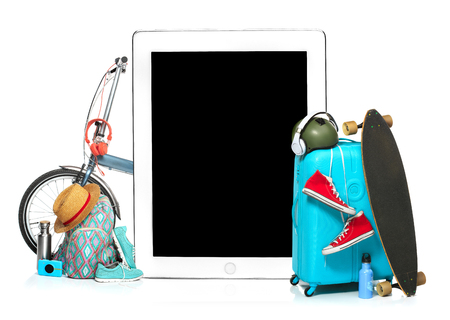 The blue suitcase, sneakers, clothing, hat, and laptop on white background. The travel, tourism and holidays concept. Collage Stock Photo