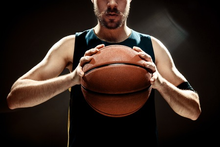 rebound: The silhouette view of a basketball player holding basket ball on black background. The hands and ball close up Stock Photo