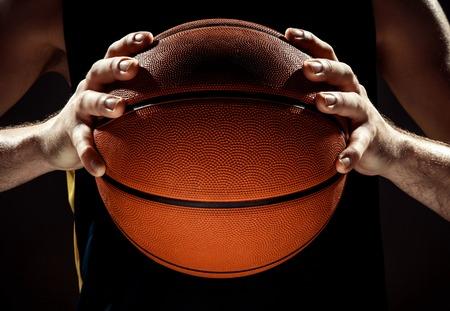 De silhouetmening van een mand van de de holdingsmand van de basketbalspeler op zwarte achtergrond. De handen en de bal sluiten omhoog Stockfoto