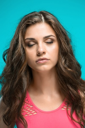 The young womans portrait with thoughtful emotions on blue background