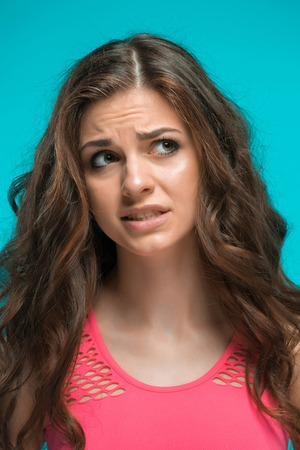 disgusted: The portrait of disgusted woman on blue background Stock Photo