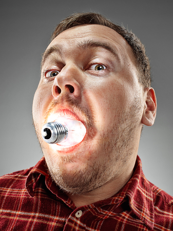 eat right: The funny caucasian man with glowing bulb in his mouth on gray background