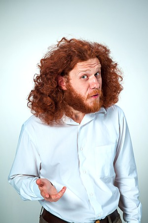 astonishment: Portrait of young man with long red hair and with shocked facial expression on gray background