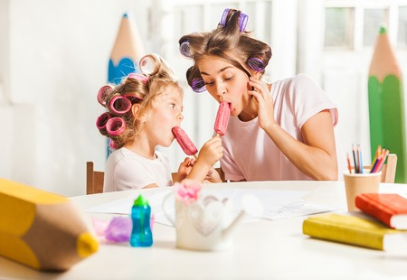 ice cream woman: Little girl eating ice cream with her mother on white Stock Photo