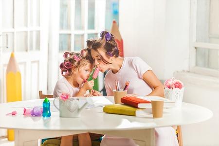 Niña que come el helado con su madre en blanco Foto de archivo - 61807928