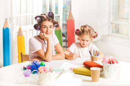 De jonge moeder en haar dochter die met potloden thuis trekken Stockfoto