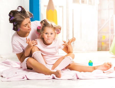 Little smiling girl playing with her mother on white Stock Photo