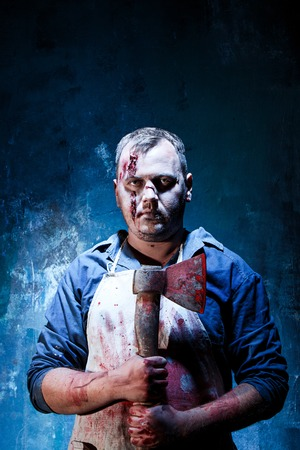 carnage: Bloody Halloween theme: crazy killer as bloody butcher with an ax on dark blue background Stock Photo