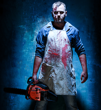 Bloody Halloween theme: crazy killer as bloody butcher with electric saw on dark blue background Stock Photo