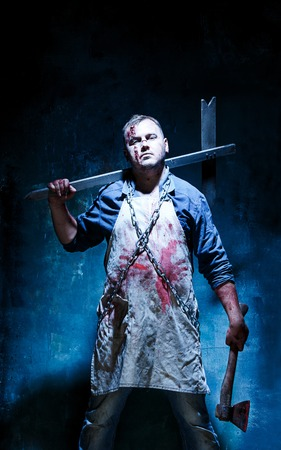 Bloody Halloween theme: crazy killer as bloody butcher with an ax on dark blue background Фото со стока