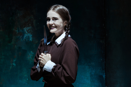 girl with knife: Portrait of a young girl with knife in school uniform as killer woman against school board . The image in the style of Halloween and Addams family Stock Photo
