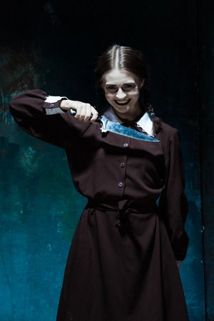 pain killers: Portrait of a young girl with knife in school uniform as killer woman against school board . The image in the style of Halloween and Addams family Stock Photo