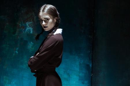 Portret van een jong meisje in schooluniform als moordenaar vrouw tegen schoolbestuur. Het beeld in de stijl van Halloween en Addams Family