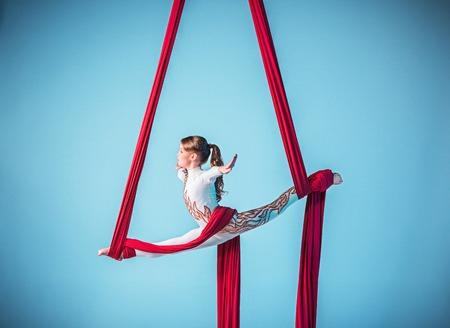 Gymnaste Graceful effectuant des exercices d'antenne avec des tissus rouges sur fond bleu Banque d'images - 62330457
