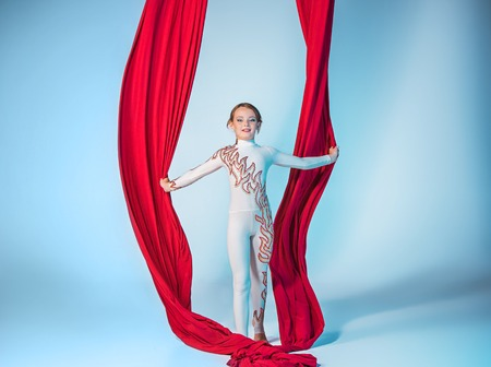 Graceful gymnast performing aerial exercise with red fabrics on blue background