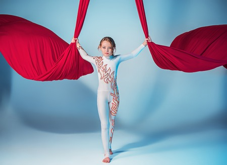Graceful Turnerin Durchführung Antenne Übung mit roten Stoffen auf blauem Hintergrund Standard-Bild - 62330865