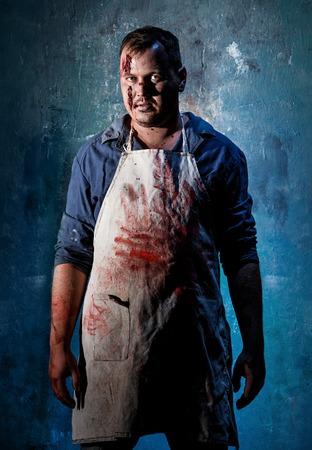 Bloody Halloween theme: crazy killer as bloody butcher on dark blue background