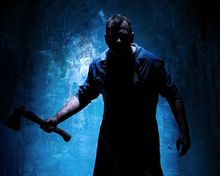 Thème Halloween sanglant: tueur fou comme boucher sanglant avec une hache sur fond bleu foncé