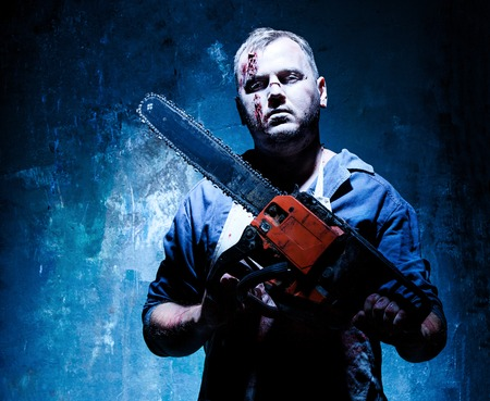 electric saw: Bloody Halloween theme: crazy killer as bloody butcher with electric saw on dark blue background Stock Photo