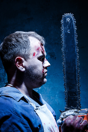 carnage: Bloody Halloween theme: crazy killer as bloody butcher with electric saw on dark blue background Stock Photo