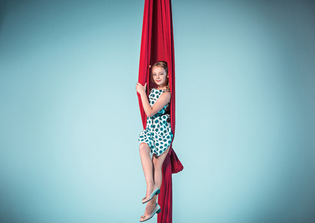 Graceful gymnast sitting with red fabrics in dress and shoes