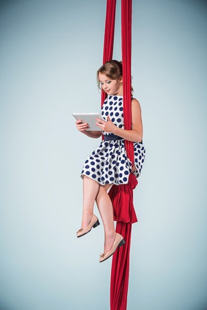 Graceful gymnast sitting on red fabrics in dress and shoes and laptop Stock Photo