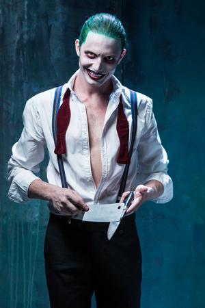 Sanglant thème de l'Halloween: Le visage joker fou sur fond noir avec un couteau Banque d'images - 62454021