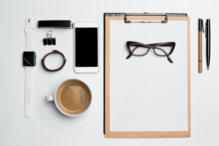 clothes organizer: Office desk table with cup, supplies, phone on white background Stock Photo