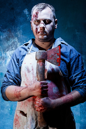 Bloody Halloween theme: crazy killer as bloody butcher with an ax on dark blue background Stock Photo