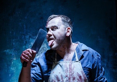 Bloody Halloween theme: crazy killer as bloody butcher with a knife on dark blue background Stock Photo