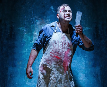 carnage: Bloody Halloween theme: crazy killer as bloody butcher with a knife on dark blue background Stock Photo