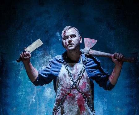 carnage: Bloody Halloween theme: crazy killer as bloody butcher with an ax and a knife on dark blue background