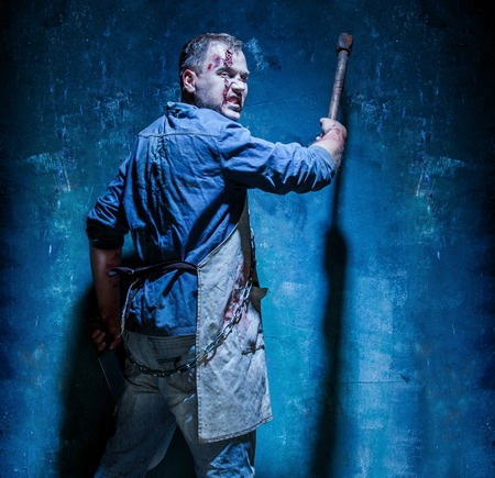 Bloody Halloween theme: crazy killer as bloody butcher with an ax on dark blue background 版權商用圖片