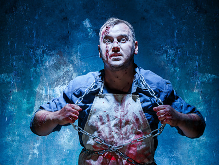 vomito: tema sangrienta de Halloween: asesino loco como cadenas de hierro carnicero vómitos con sangre sobre fondo azul oscuro