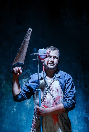Bloody Halloween theme: crazy killer as bloody butcher with saw on dark blue background