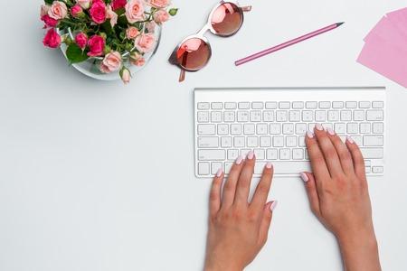 Bureau table de bureau avec les femmes mains, ordinateur, matériel, fleurs. Vue de dessus avec copie espace Banque d'images - 62346336